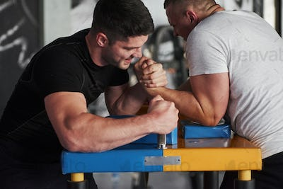 Strength comparison. Arm wrestling challenge between two men. Match on a special table