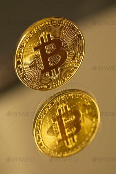 Gold Bitcoin Cryptocurrency Coin With Reflection On Mirror