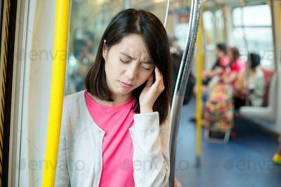 Woman feeling headache inside train compartment