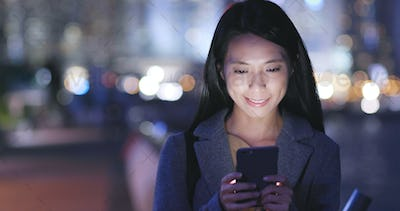 Young Woman use of cellphone in city at night