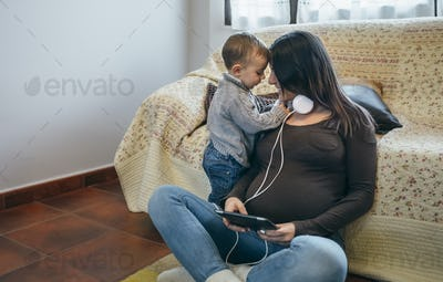 Toddler claiming the attention of his pregnant mother