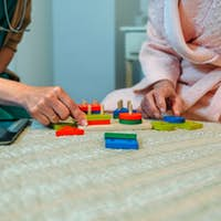 Female doctor showing geometric shapes to elderly patient