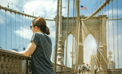 Woman looking cityscape from Brooklyn Bridge in New York City