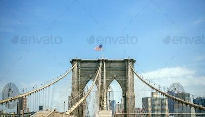 Brooklyn Bridge towers with Manhattan skyline on background