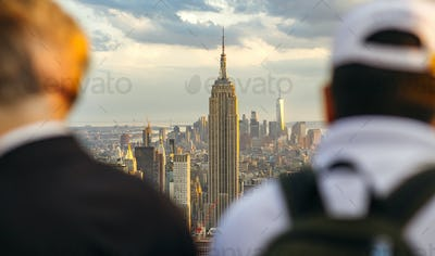 The Empire State Building in Manhattan between two unrecognizable men in foreground