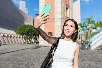 Woman taking selfie in Hong Kong with clock tower