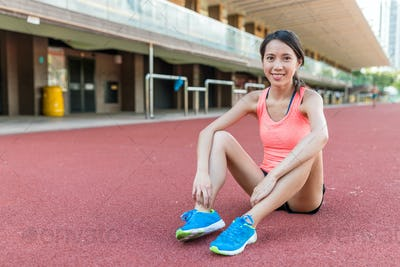Woman taking rest and sitting down on sport court