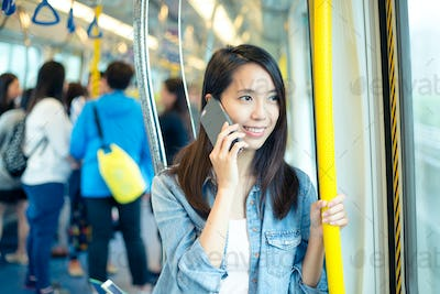 Asian woman talk to mobile phone inside train