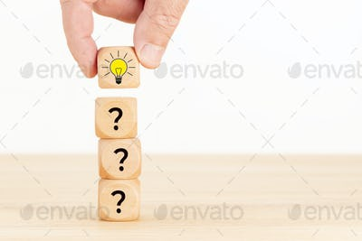 Hand picked wooden cube block with question mark symbol and light bulb icon