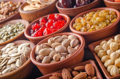 Different nuts seeds and dried fruits in bowls on kitchen table