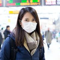 Woman wearing face mask inside train station
