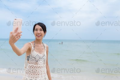 Woman taking selfie by mobile phone from the beach