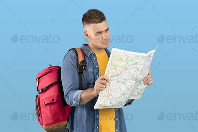 Pensive young backpacker looking at map with concern, feeling lost, cannot find his travel