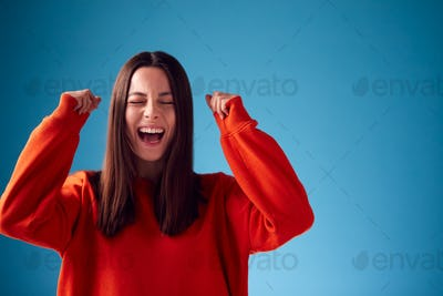 Excited Young Woman Celebrating And Pumping Fists In The Air Against Blue Studio Background
