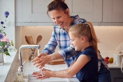 Mother And Daughter Washing Hands With Soap At Home To Stop Spread Of Infection In Health Pandemic