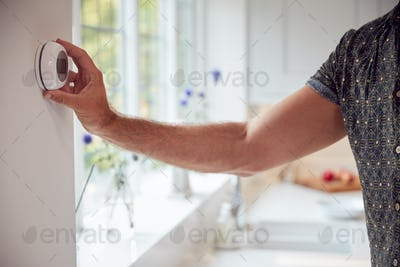 Close Up Of Man Adjusting Wall Mounted Digital Central Heating Thermostat Control At Home