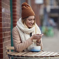 Female Customer Sending Text Message Sitting Outside Coffee Shop On Busy City High Street In Fall