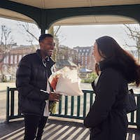 Romantic Man Surprising Young Woman With Bouquet Of Flowers As They Meet In City Park