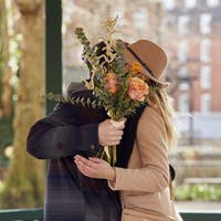 Romantic Man Hugging Young Woman With Faces Hidden Behind A Bouquet Of Flowers He Gives Her