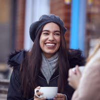 Two Female Friends Meeting Sitting Outside Coffee Shop On City High Street
