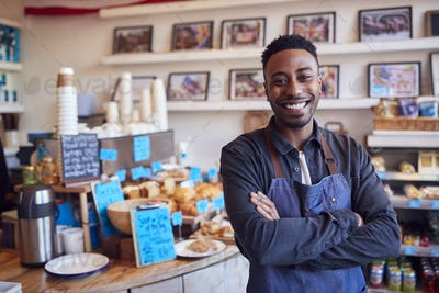 Portrait Of Smiling Male Owner Of Coffee Shop Standing By Counter