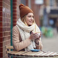 Female Customer Sitting Outside Coffee Shop On Busy City High Street In Fall