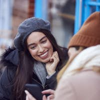 Two Female Friends Meeting Outside Coffee Shop On City High Street Looking At Mobile Phone
