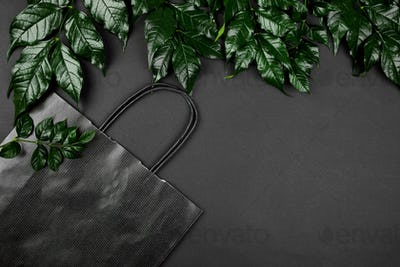 Mockup of black shopping bag on a dark background with green leaves