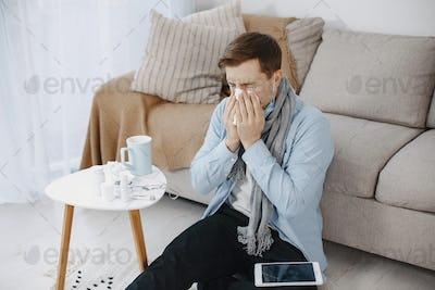 Sick man sitting on sofa at home