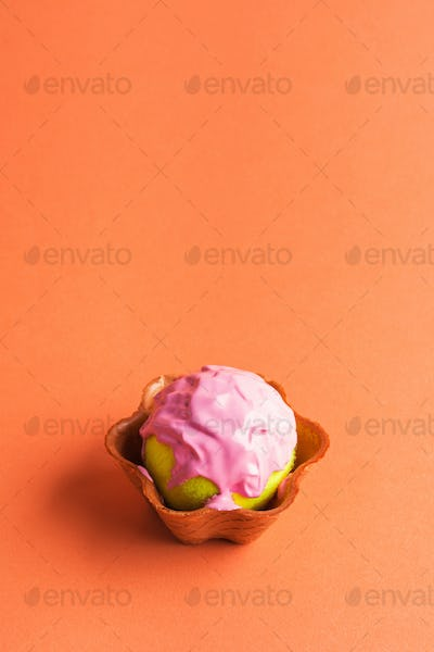 Tennis ball with pink paint in waffle cup