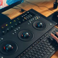 Video editor hands adjusting color or sound on working console machine