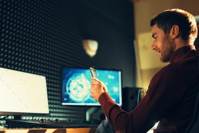 Young man working in the studio using a smartphone and computer.
