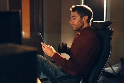 Young man working at home using a smartphone and computer.