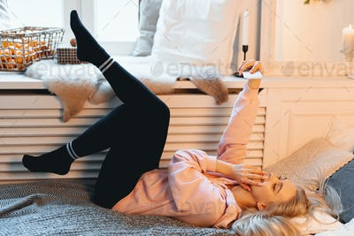 Coquette young girl having fun, making selfie while lying on the