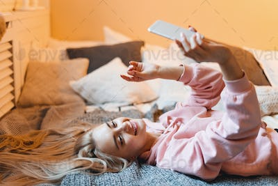 Pretty young girl having fun, making selfie with smart phone while lying on the bed at home