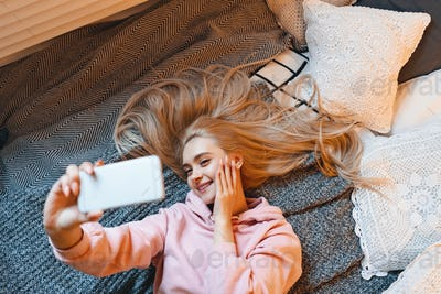 Pretty young girl having fun, making selfie with smart phone whi