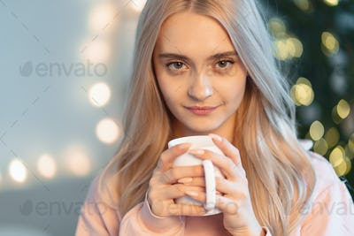 A pretty young woman making a wish while drinking a hot cup of m