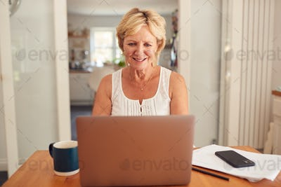 Retired Woman At Home In Kitchen Shopping Online And Managing Domestic Finances Using Laptop