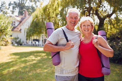 Portrait Of Senior Couple At Home In Garden Wearing Fitness Clothing Ready For Outdoor Yoga Session