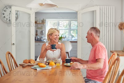 Retired Couple At Home In Kitchen Eating Breakfast Together