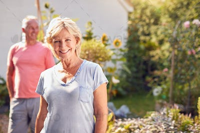 Portrait Of Retired Couple Working In And Enjoying Summer Garden At Home