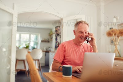 Retired Man On Phone At Home In Kitchen Using Laptop