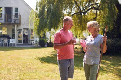 Retired Man Bringing Cold Drink To Woman Tidying Garden With Rake