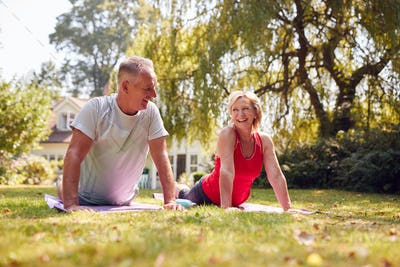 Senior Couple At Home In Garden Wearing Fitness Clothing Enjoying Outdoor Yoga Class