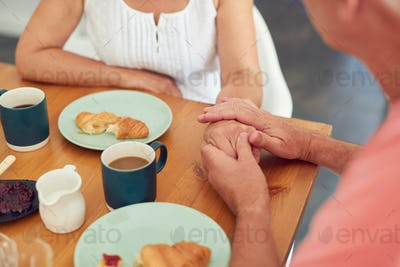 Close Up Of Senior Man Comforting Woman Suffering With Depression At Breakfast Table At Home