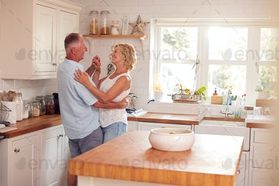 Retired Romantic Couple Dancing In Kitchen At Home Together