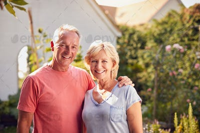 Portrait Of Loving Retired Couple Working In And Enjoying Summer Garden At Home