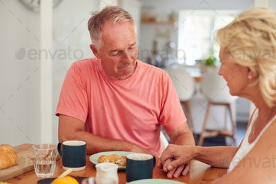 Senior Woman Comforting Man Suffering With Depression At Breakfast Table At Home