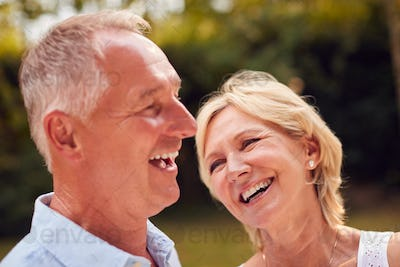 Portrait Of Laughing Senior Couple In Garden At Home Together