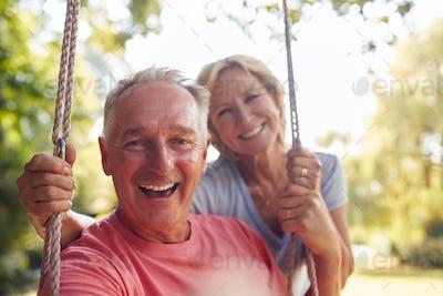 Portrait Of Retired Couple Having Fun With Woman Pushing Man On Garden Swing